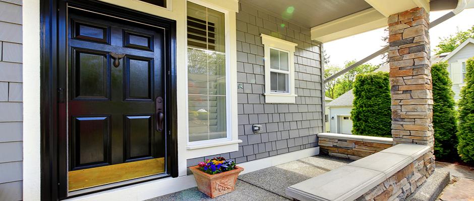 Grey house exterior with black door.
